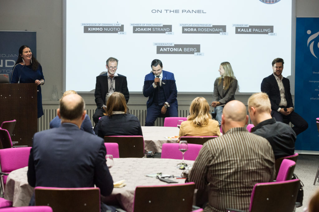 Panel of five people talking infront of and audience.
